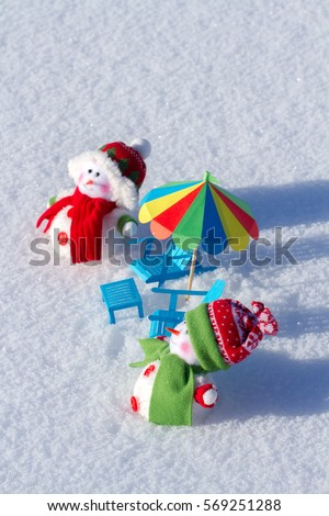 Two cute snowman sunbathing in the snow. Paper chairs and beach umbrella
