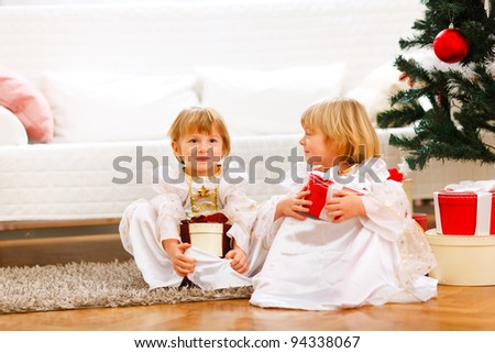 Two cute twins girl sitting with presents boxes near Christmas tree