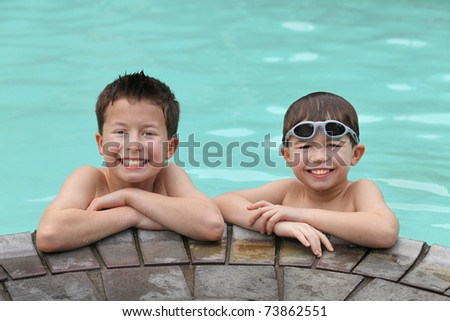 two cute young boys at the edge of a swimming pool