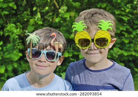 Two cute young brothers wearing funny, novelty sunglasses - stock photo