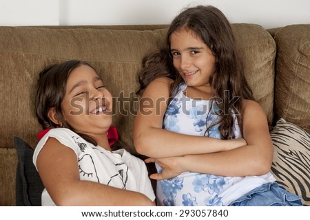 Two cute young girls in the sofa .