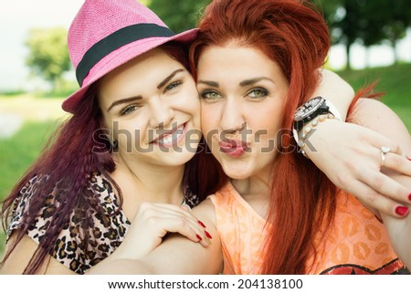 Two cute young women taking a selfie in park on sunny summer day. Closeup photograph of two female friends hugging smiling taking a selfie. Caucasian redhead and brunette women portrait. - stock photo