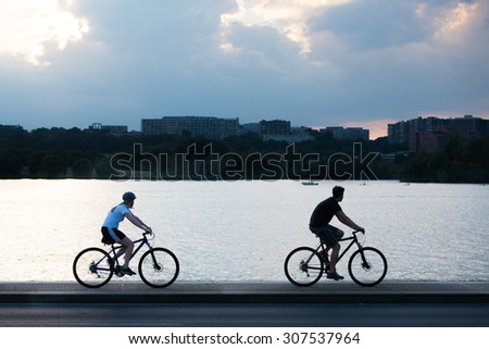 Two cyclist silhouette at bike way alongside the Potomac River in Washington DC, USA - stock photo