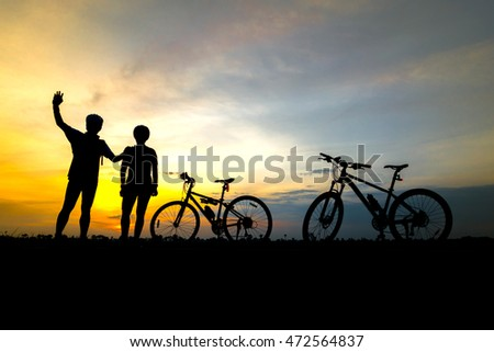 Two cyclists and two bicycle  silhouettes on the background of sunsets