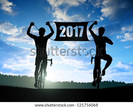 Two cyclists on bicycle at sunset. Forward to the New Year 2017