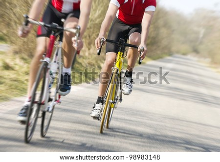 Two cyclists on road racing bicycles in pursuit, focus on the cyclist in the center, motion blurred image