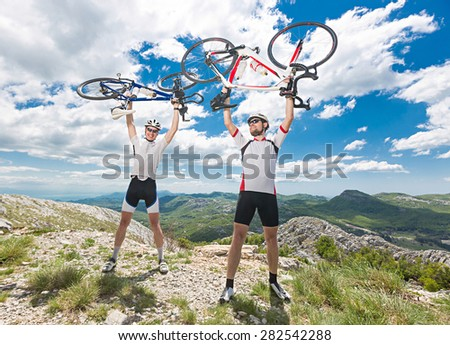 two cyclists overcome ascent of Mount celebrating victory - stock photo