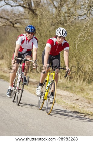 Two cyclists racing closely together at high speed - stock photo