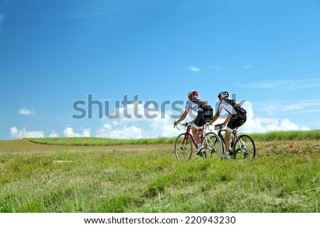 Two Cyclists ride on road in south France in summer sunny day against bright blue sky