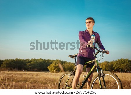 two cyclists riding on a dirt road - stock photo