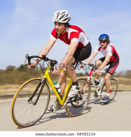 Two cyclists sprinting past the camera at high speed - stock photo