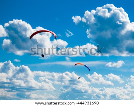 Two dark paraglide silhouettes on background of blue summer sky and white clouds. Adrenalin sport theme. - stock photo