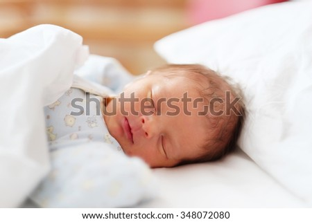 Two days old newborn baby in bed