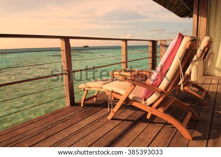 Two deck chairs on a sea view balcony at a tropical resort in Maldives.