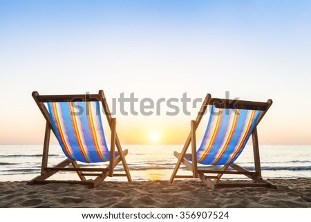two deck chairs on a tropical sandy beach with beautiful colorful sunset