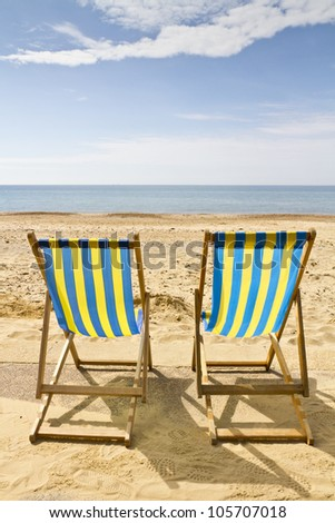 Two deck chairs on the beach at Bournemouth, Dorset,UK on a bright sunny summer day - stock photo