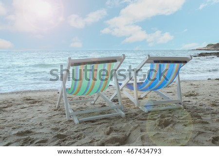 Two deckchairs on beach, facing out to sea