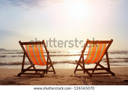 Two deckchairs on the beach with bright sun and waves - stock photo
