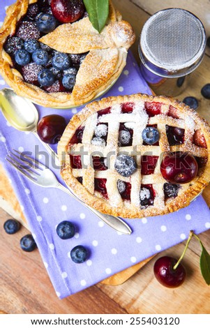 Two decorated homemade shortcrust pastry berry pies with polka dot cloth, shiny metal icing sugar shaker, fork, spoon and selection of berries on grunge style wooden table. - stock photo