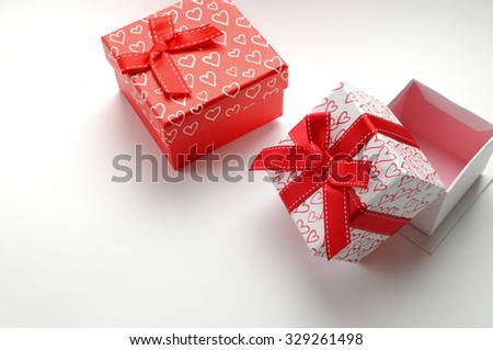 Two decorative gift boxes with red ribbon and hearts printed. Top view right. White isolated background.