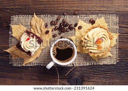 Two delicious cakes and cup of hot coffee on wooden table. Top view - stock photo