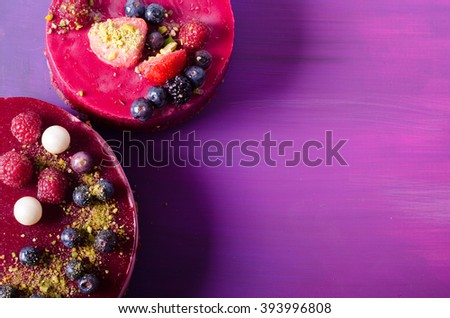 Two delicious cakes with fresh berries, raspberries, blueberry, currants and pistachios on bright background. Free space for your text. - stock photo