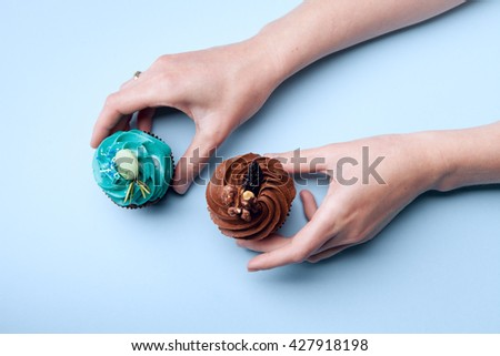 Two delicious cupcakes with cream in hands on a blue background - stock photo