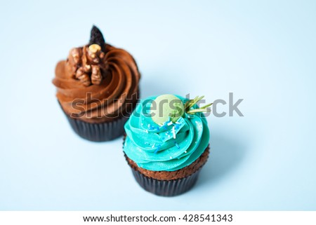 Two delicious cupcakes with cream on a blue background