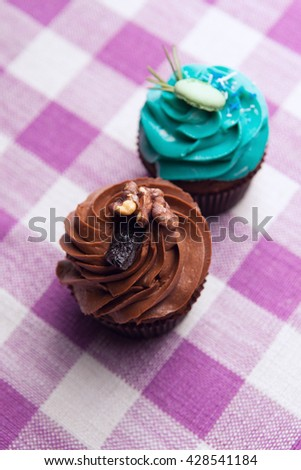 Two delicious cupcakes with cream on the tablecloth - stock photo
