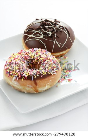 Two delicious donuts against a bright background with copy space. One covered in thick dark chocolate the other with multi-coloured sugar candy sprinkles. - stock photo