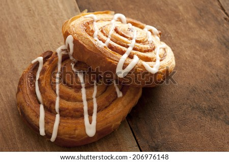 Two delicious freshly baked Danish pastries filled with apple or almond and drizzled with white icing on a rustic wooden kitchen counter ready for a tasty teatime snack - stock photo