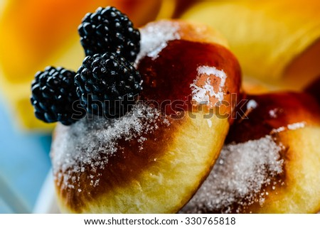 two delicious german doughnuts with blackberry and blackberry sauce and yellow napkin