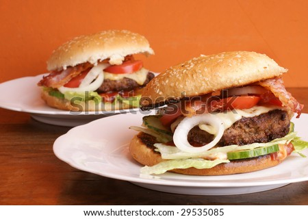 Two delicious hamburger with salads and bacon - stock photo