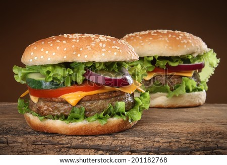 Two delicious hamburgers on wood background. - stock photo