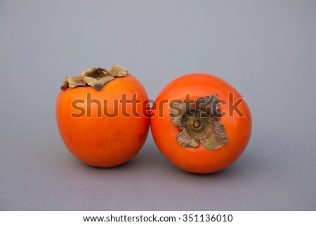 Two delicious ripe organic persimmons, your perfect winter vitamine bomb. Grey  background. Natural light. Selective focus. - stock photo