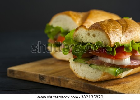Two delicious sandwiches with baguette, ham, tomato, onion, cucumber and lettuce on wooden table. Fast food - stock photo