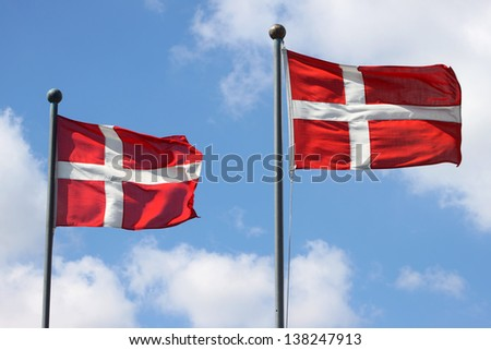 Two Denmark flags waving on wind against the blue sky with clouds