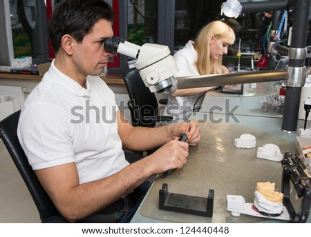 Two dental technicians at their workplace polishing dental prosthesis - stock photo
