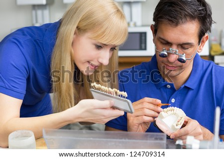 Two dental technicians with colour samples choosing the right colour for dental porcelain - stock photo