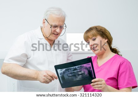 Two dentist doctor analyzing X-ray - healthcare and medical concept - stock photo