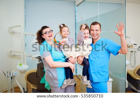 Two dentist with children in their arms smiling, laughing  the d