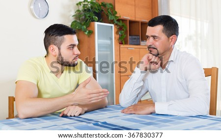 Two despair male adults arguing about something in living room
