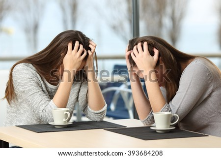 Two desperate sad girls crying with hands over head in a bar with a window with a winter background - stock photo