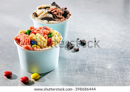 Two dessert take out containers filled with creamy frozen italian gelato topped with candy pieces and cookie crumbles