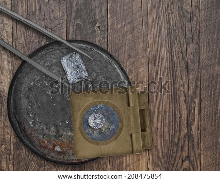 two diamonds in a vintage tin, tweezers and loupe on a wooden bench, space for your text - stock photo