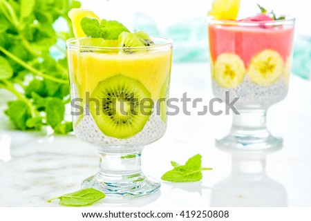 two different Chia seed puddings in a glass with kiwi strawberry on white table. fresh blended fruit smoothies made with pineapple, banana, coconut, turmeric and chia seeds on a summer background.  - stock photo
