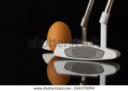 Two different golf putters and egg on a black glass desk - stock photo
