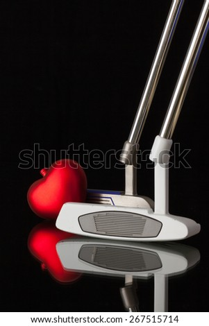 Two different golf putters and red heart  on a black glass desk - stock photo
