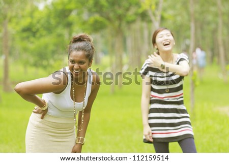 Two different races woman laughing, black and asian. - stock photo