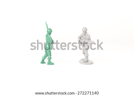 Two different toy army men cross paths - stock photo